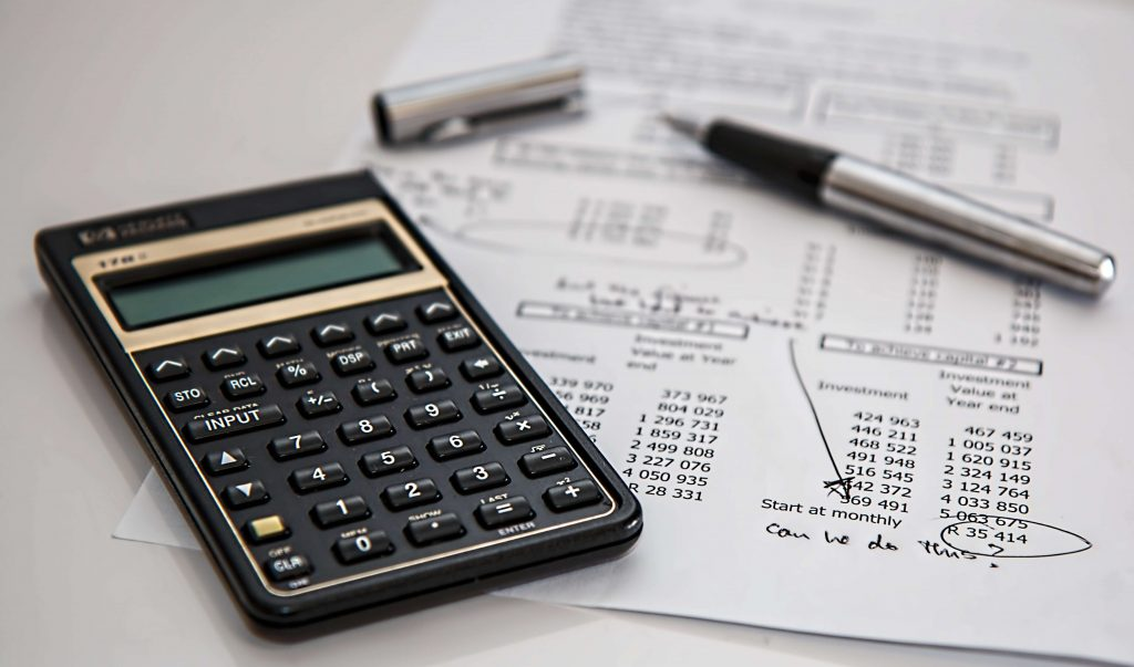 Calculator, pen, and land loan documents on a table